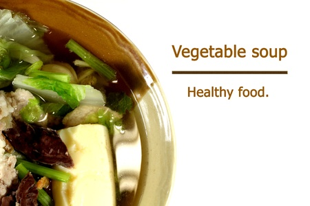 Vegetable soup in a brown bowl. A white background. photo