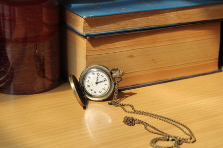 Books on antique clocks on the desk in vintage style. photo