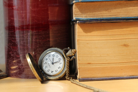 Books on antique clocks on the desk in vintage style.