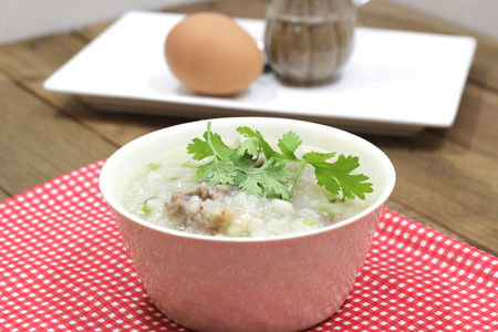Rice Soup with pork and machines in a white Cup. With eggs and cooked as a visual component. photo