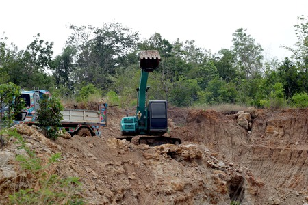 earth moving equipment: Backhoe the excavator in action in the forest.