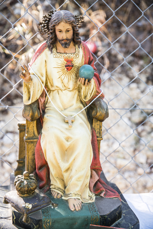 On the street and among a mesh fence the almighty are of God Sculpture of wood of Jesus Christ, are of god sitting on the throne