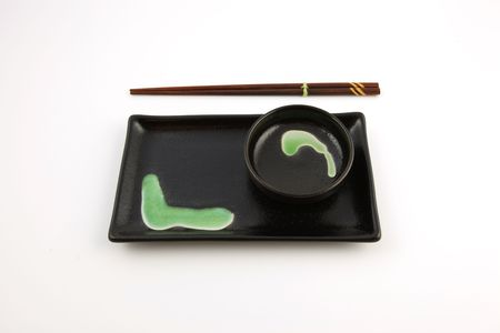 A green and black sushi plate and bowl with wooden chopsticks