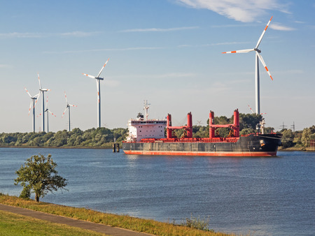electricity export: Container ship on a river with wind turbines in the background
