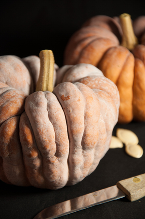 Two pumpkins and a knife isolated on black background Stock Photo