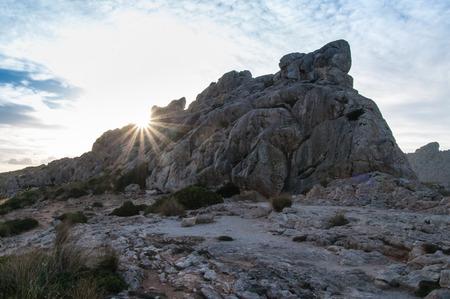 Sun beams behind a mountain at Mallorca, Spain, at twilight