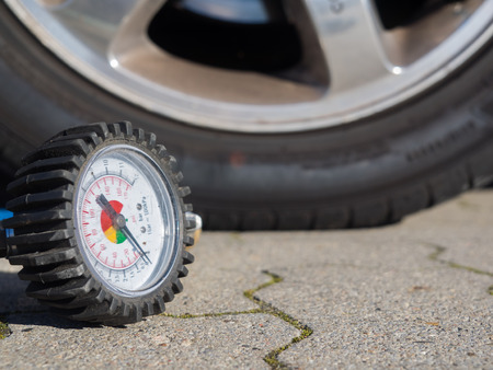 air pressure: Closeup of a tire of a car and the scale of a compressor to measure air pressure Stock Photo