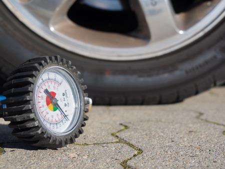 Closeup of a tire of a car and the scale of a compressor to measure air pressure Standard-Bild