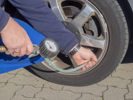 air pressure: A man is measuring the air pressure of the tire of a car Stock Photo