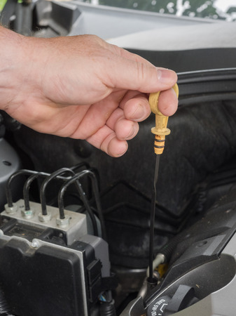 landscape format: Someone is mearuring the oil level of a car