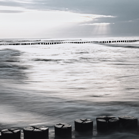 Monochrome image of the Baltic Sea with breakwaters at sunset Stock Photo