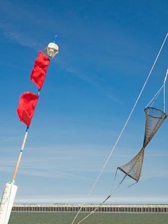 Details van een vissersboot: boeien met rode vlaggen en visnet