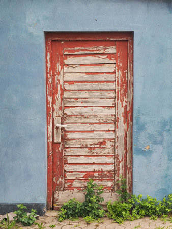 red door with paint flaking off in a red wall