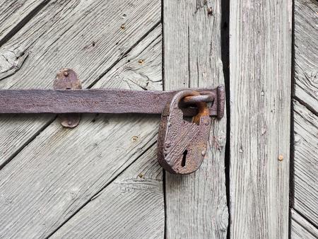 Rusty padlock at wooden door