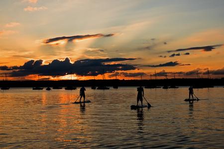 Three stand-up paddler at Lake Starnberg, Bavaria, at sunset