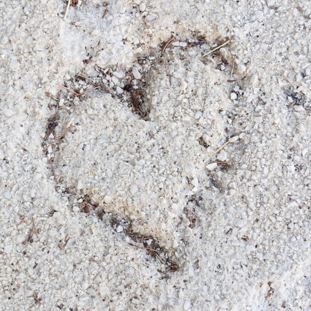 Heart drawn in sand as a symbol of love