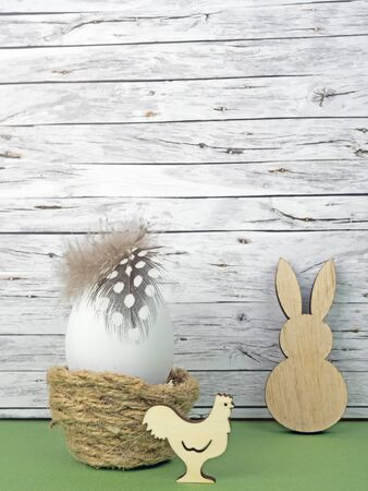 Easter background with Easter egg, Easter bunny  and cock isolated on green in front of wood Standard-Bild
