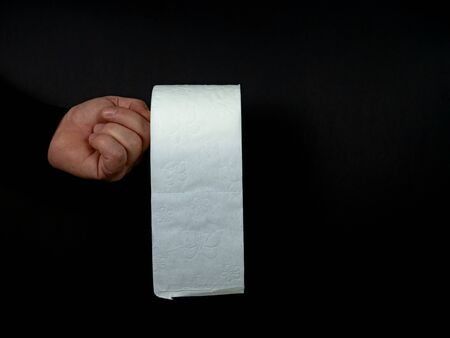Hand of a man holds one roll of white toilet paper isolated on black background Standard-Bild