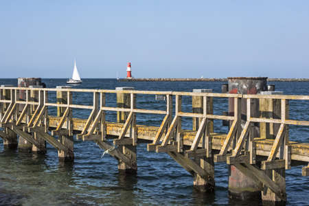 Baltic Sea with wooden pier, lighthouse and sailing ship at Rostock Warnemuende, Germany