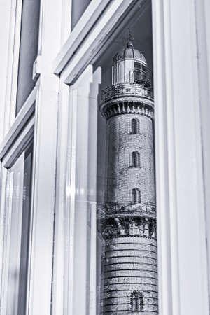 Mirroring of the old lighthouse of Rostock Warnemuende in a window glass, monochrome
