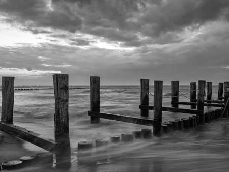 Monochrome image of a groyne in the Baltic Sea near to Zingst, Mecklenburg-Western Pomerania, at twilight