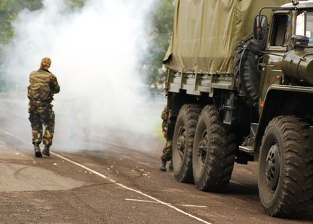A person wearing generic military outfit near a a military style truck checks something in a cloud of smoke photo