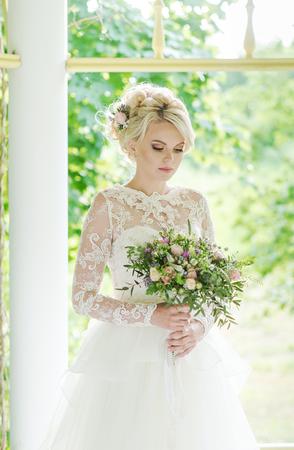 cabello rubio: Beautiful blonde bride in a luxurious dress with wedding bouquet. Foto de archivo