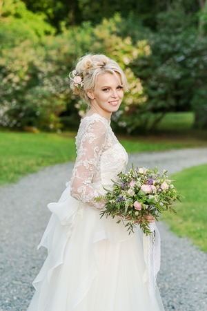 sexy bride: Beautiful blonde bride in a luxurious dress with wedding bouquet. Stock Photo