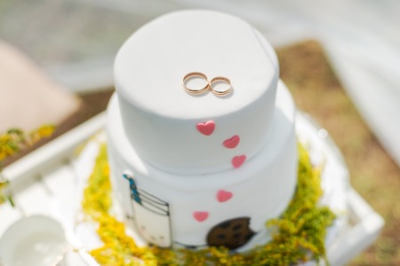 ślub: Funny wedding cake from mastic with a cup of milk and cookies. White wedding cake with flowers.