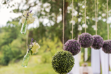 wedding decor: Flower round compositions for wedding decor. Glass hanging bottles for flowers. Stock Photo