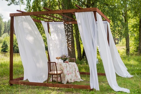 arranging chairs: Outdoor gazebo with white curtains. Wedding decorations. Art object.