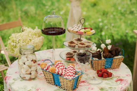 Dessert table for a party. Chocolate cake, cupcakes, sweetness, macaroons, marshmallows, zephyr and flowers.