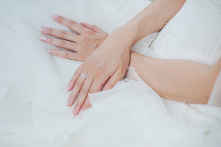 white gold: White gold ring with diamonds on the hand of the bride. Bride in white dress. Stock Photo