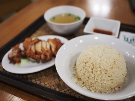 focuses: A set of fried chicken rice with soup, this photo focuses on a bow of rice and blurred on fried chicken and a cup of soup Stock Photo