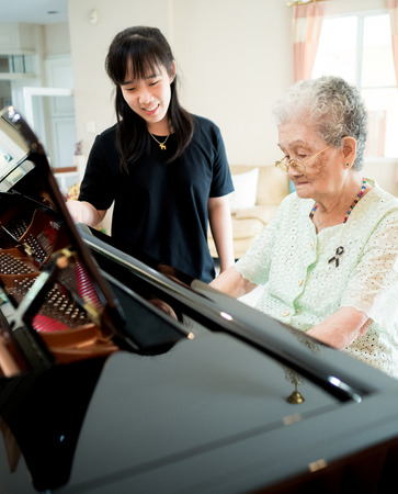 senior woman learns to plays piano from her nephew at home with smile and happiness Reklamní fotografie