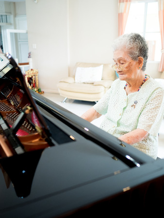 senior woman pianist plays piano at home with smile and happiness