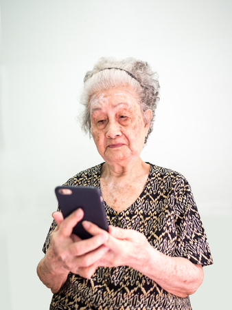 Old Asian woman reads the message and play social on the phone Reklamní fotografie