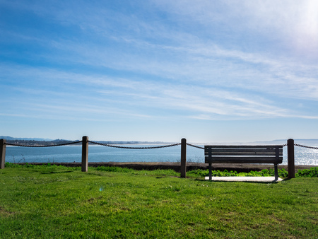 Lonely Bench on grass with blue sky. Looking out to the empty space, sea, ocean.