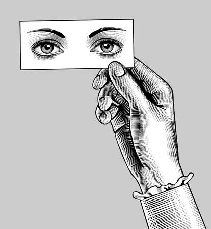 Mano femenina sosteniendo una tarjeta con dibujo de ojos. Dibujo estilizado de grabado vintage. Ilustración vectorial