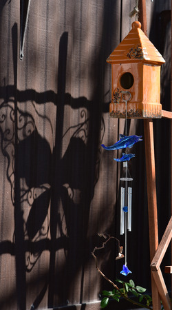 A ceramic birdhouse, a dolphin wind chime and a butterfly shadow make for an eccentric display. Stock fotó