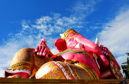 Big Pink colors of Hindu god lord Ganesha with white cloud and blue sky background from Thailand Stock Photo