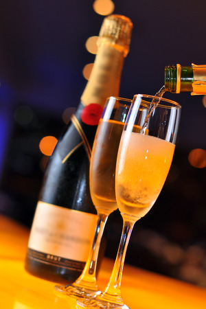 Pouring Champagne into tall glass Stock Photo