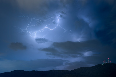 Lightning over a mountain during thunderstorm at night Stock Photo