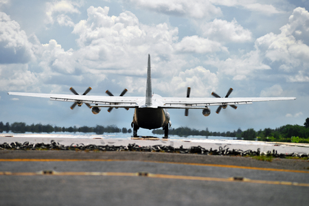 Military transport aircraft landing on runway