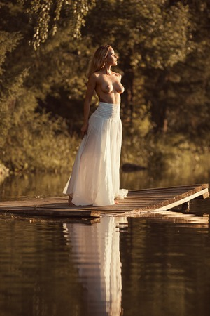 Sensual young woman with beautiful naked breasts standing nude on wooden platform by the lake at sunset or sunrise