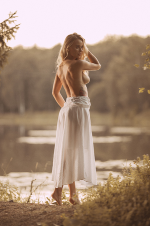 Sensual young woman with beautiful body standing topless naked or nude by the lake at sunset showing her back
