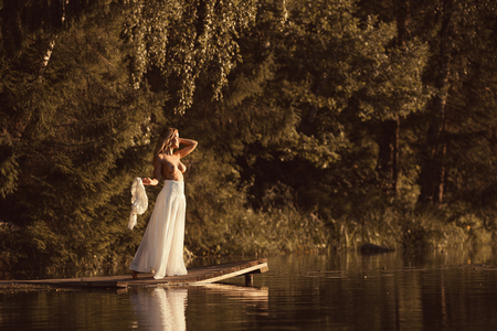 Attractive young woman with beautiful naked body standing nude on wooden platform by the lake at sunset or sunrise