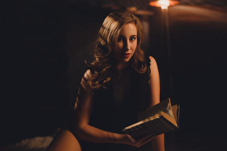 Beautiful young woman with long brown hairs sitting in black sexy lingerie on a carpet under bookshelf reading a book lit by floot lamp on a dark background.