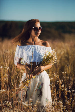 Sexy young woman with slim athletic body in sunglasses standing posing in the meadow on sunset handing bouqet