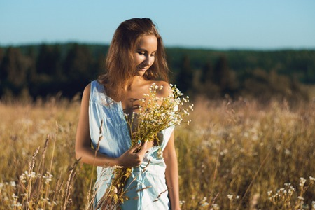Sensual young girl in sleeveless jean sundress standing in field of tall grass covering naked breasts by bouquet